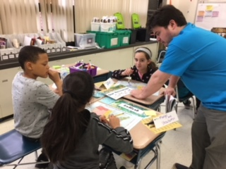 Fourth graders working with a JA volunteer